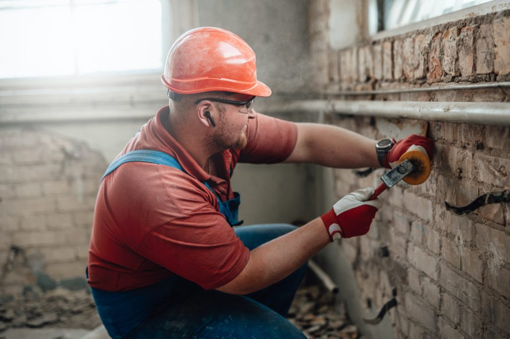 Builder on a construction site working on a brick wall with a hammer