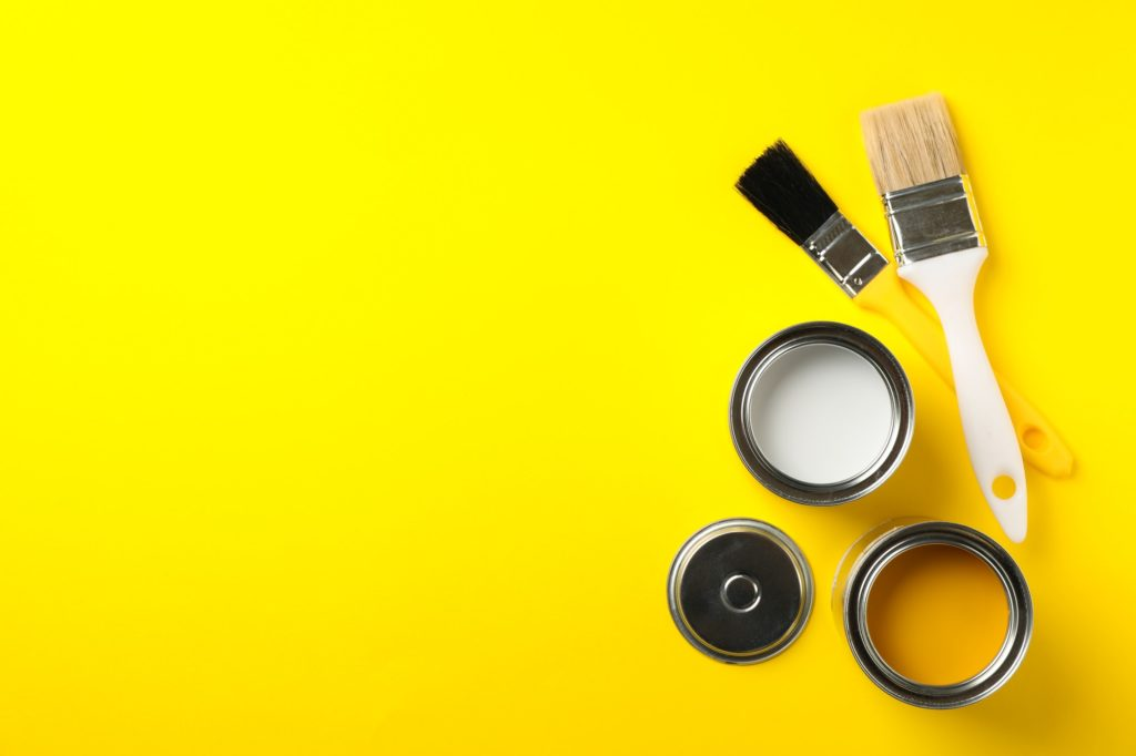 Cans of paints and brushes on yellow background, top view