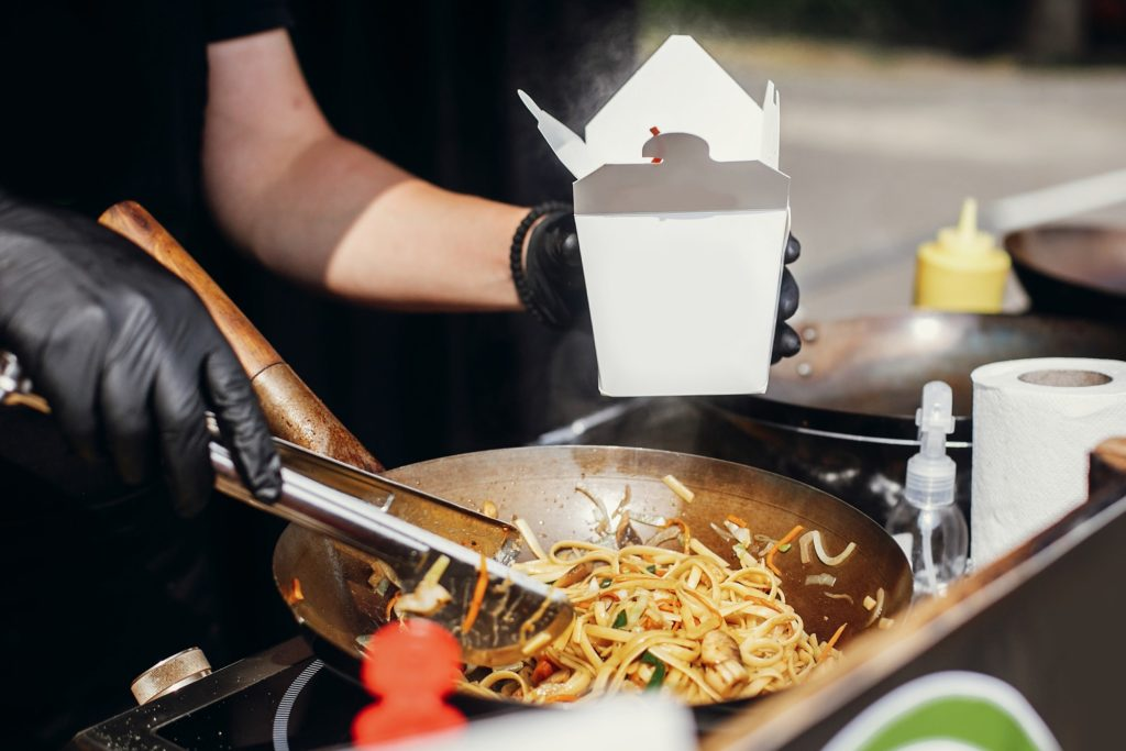 Chef putting noodles in carton box to go from pan on fire at open kitchen