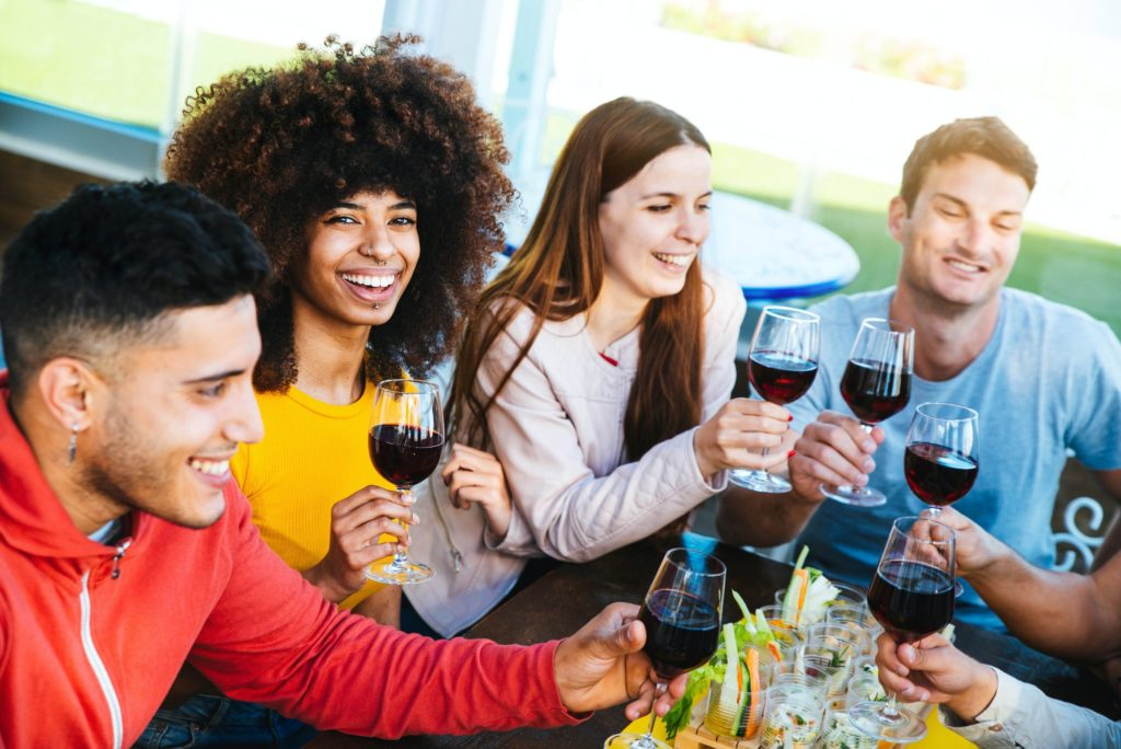 Diverse young people celebrating drinking wine at bar restaurant