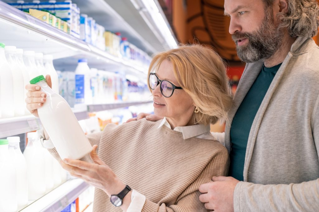 Mature husband and wife choosing together fresh dairy products by display