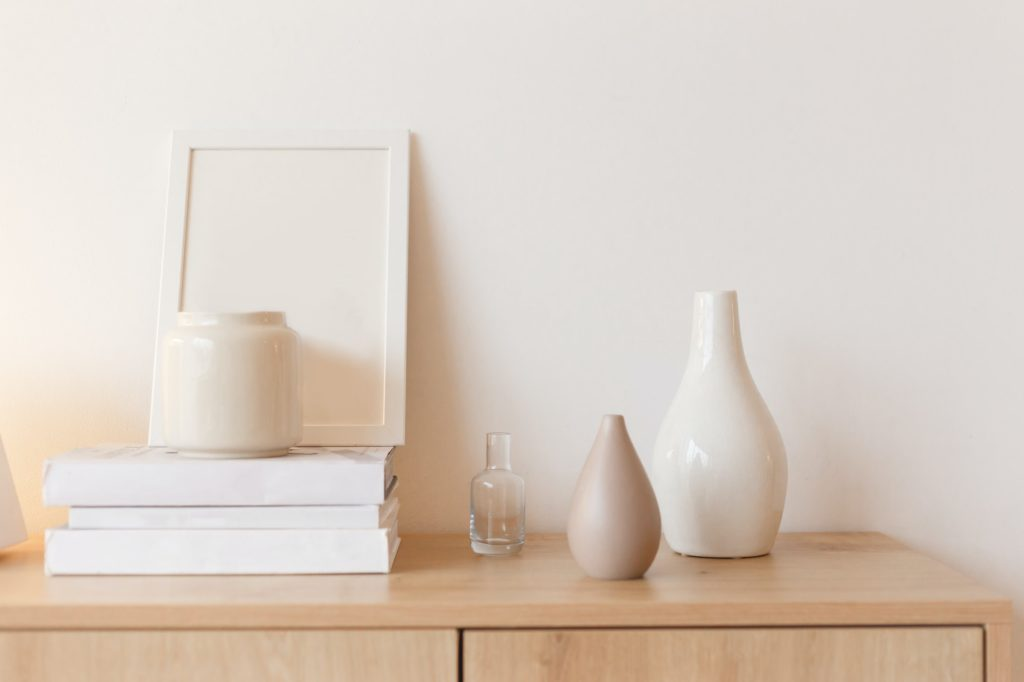 Neutral colored vases, photo frame and stack of books on bureau shelf