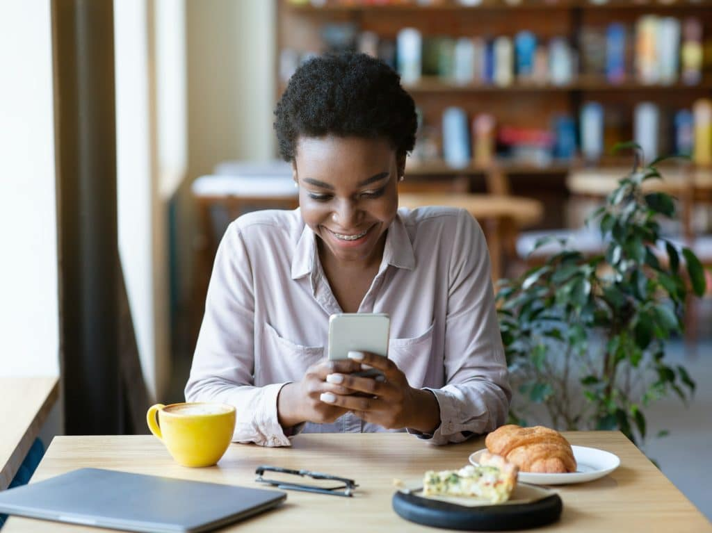 Young African American woman with smartphone chatting online, browsing web, checking social media at