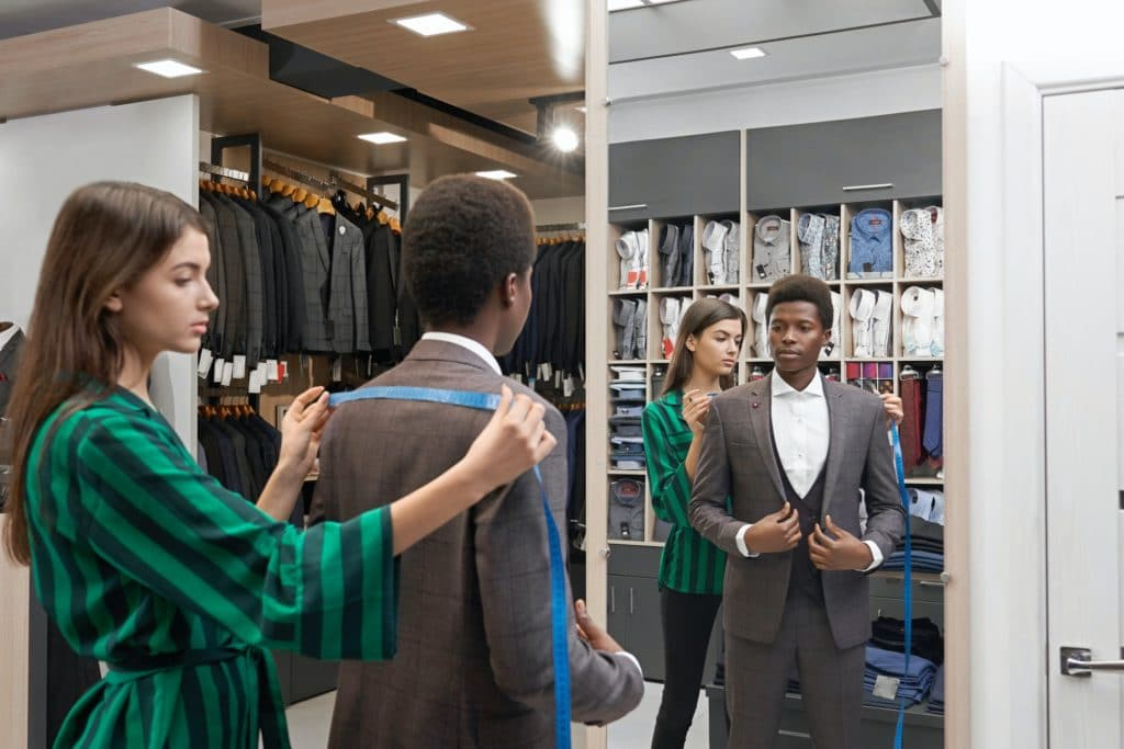 Client in shop in elegant suit looking at mirror