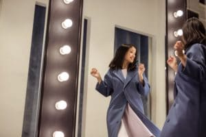 Happy beautiful woman at the mirror